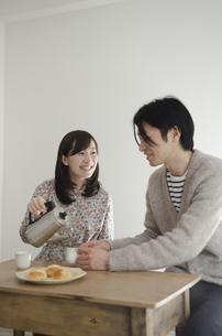 男性のカップにお茶をつぐ女性 FYI01077132