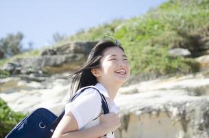 カバンを肩に掛けて笑う制服姿の女の子 FYI01077136