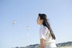 かもめをバックにビーチで微笑む制服姿の女の子の素材 [FYI01077158]