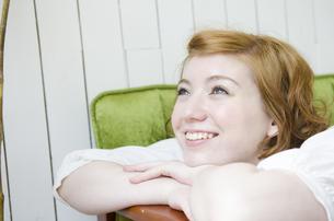 緑のソファに手を掛けて笑うハーフの女性 FYI01077164