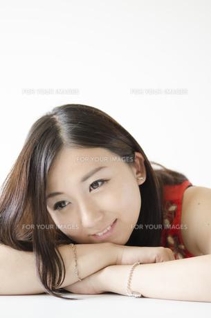 机の上に腕を組み顔を乗せて笑う女性 FYI01077173