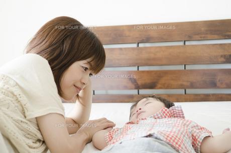 ベッドで寝かしつけるお母さんと眠る男の子 FYI01077177