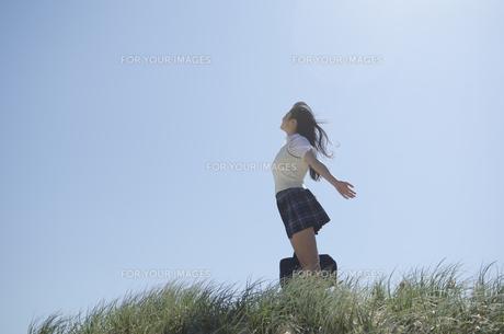 草むらに立って手を広げている制服姿の女の子 FYI01077179