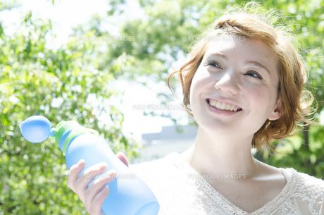ウォーターボトルを持って笑うハーフの女性 FYI01077181