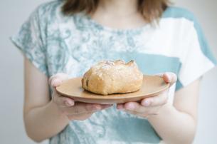 お皿に乗ったパンを持つ女性の手元 FYI01077186
