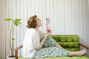 緑のソファに座ってさくらんぼを食べようとしているハーフの女性 FYI01077193
