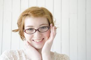 メガネのふちを持って笑うハーフの女性 FYI01077194
