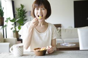 フルーツサラダを笑顔で食べる女性 FYI01077197