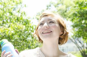 ウォーターボトルを持って笑うハーフの女性 FYI01077214