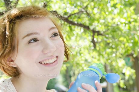 ウォーターボトルを持って笑うハーフの女性 FYI01077223