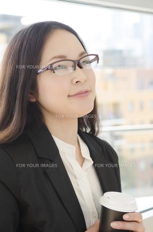 コーヒーカップを手に微笑む眼鏡をかけた女性 FYI01077229