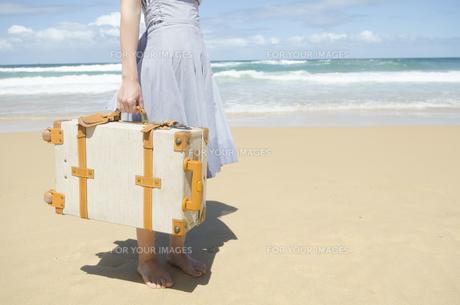 波打ち際をスーツケースを持って歩く女性の下半身 FYI01077231