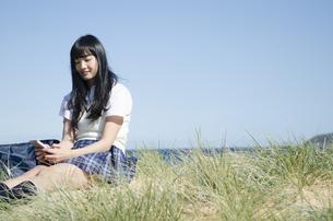 ビーチに座って携帯電話をいじっている制服姿の女の子 FYI01077232