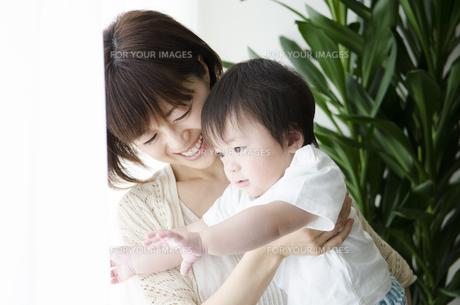 部屋の中で男の子を抱っこするお母さん FYI01077234