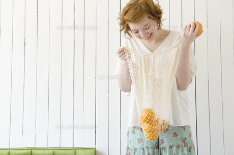 網の袋に入ったオレンジを見て笑うハーフの女性 FYI01077236