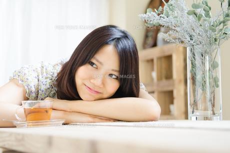 テーブルでリラックスしている女性 FYI01077250