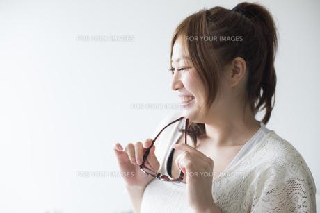 メガネを持って笑う女性 FYI01077253