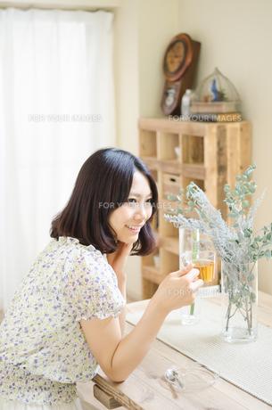 テーブルでお茶を飲んでいる女性 FYI01077254