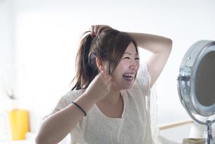 鏡を見ながら髪を結ぶ女性 FYI01077257