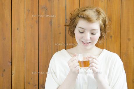 両手で持ったコップを見るハーフの女性 FYI01077262