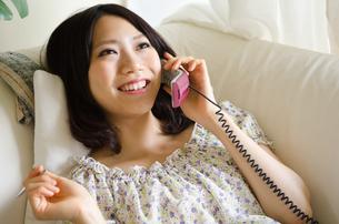 部屋の中で電話をしている笑顔の女性 FYI01077266