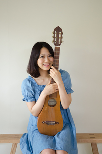 ギターを抱えている笑顔の女性 FYI01077271
