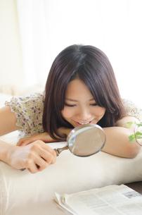 虫眼鏡で新聞を見ている女性 FYI01077277