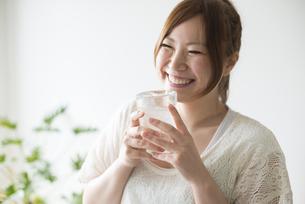 水の入ったコップを持って笑う女性 FYI01077278
