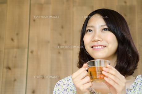 お茶の入ったグラスを持って笑う女性 FYI01077280