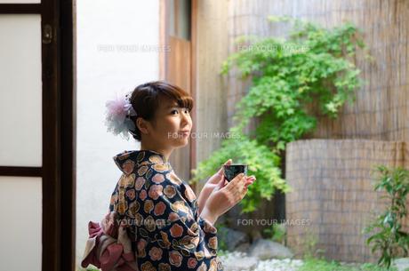 縁側に座ってお茶の入った湯のみを持つ着物姿の女性 FYI01077286