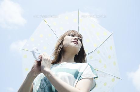 青空をバックに傘を差した女性 FYI01077290