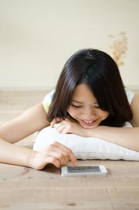 床に寝そべってスマートフォンを操作する女性 FYI01077294