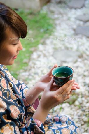 お茶の入った湯のみを持つ着物姿の女性 FYI01077302