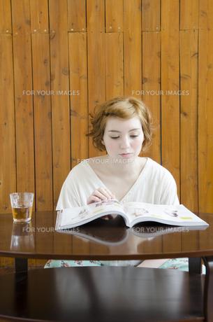 部屋の中で雑誌を読むハーフの女性 FYI01077305