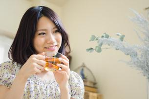 お茶の入ったグラスを持って笑う女性 FYI01077306