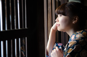 格子の窓から外を見る着物姿の女性 FYI01077310