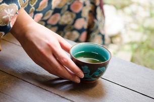 お茶の入った湯のみと女性の手 FYI01077311