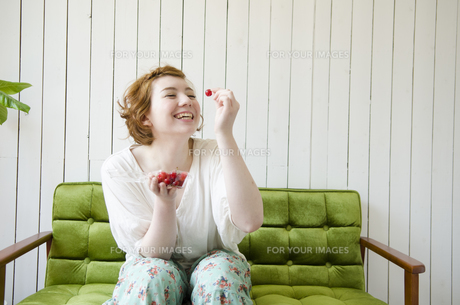 緑のソファに座ってさくらんぼを持って笑うハーフの女性の素材 [FYI01077315]