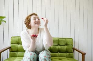緑のソファに座ってさくらんぼを持って笑うハーフの女性 FYI01077315