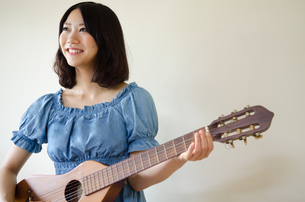 ギターを持っている笑顔の女性 FYI01077317