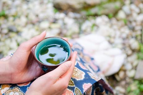 お茶の入った湯のみと女性の手 FYI01077318