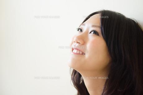 上を見上げて笑う女性 FYI01077320