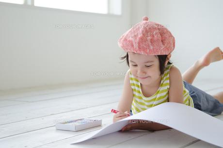 床に寝そべって絵を描く女の子 FYI01077321