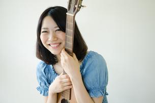 ギターを抱えている笑顔の女性 FYI01077326