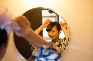 鏡を見ながら髪の毛を直す着物姿の女性 FYI01077327