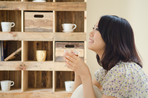 お茶の入ったグラスを持って笑う女性 FYI01077336