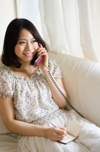 部屋の中で電話をしている女性 FYI01077338