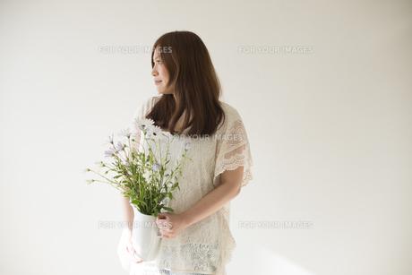 ポットに入った白いデイジーを持つ女性 FYI01077343
