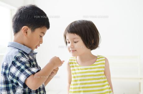 男の子の手元を覗き込む女の子 FYI01077352