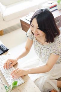 床に座ってパソコンを操作している女性 FYI01077360